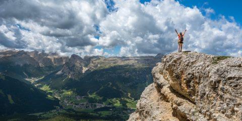 山の頂上で両手を上げる女性