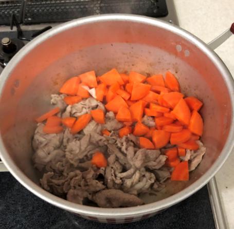 鍋に入れた切ったにんじんと牛肉