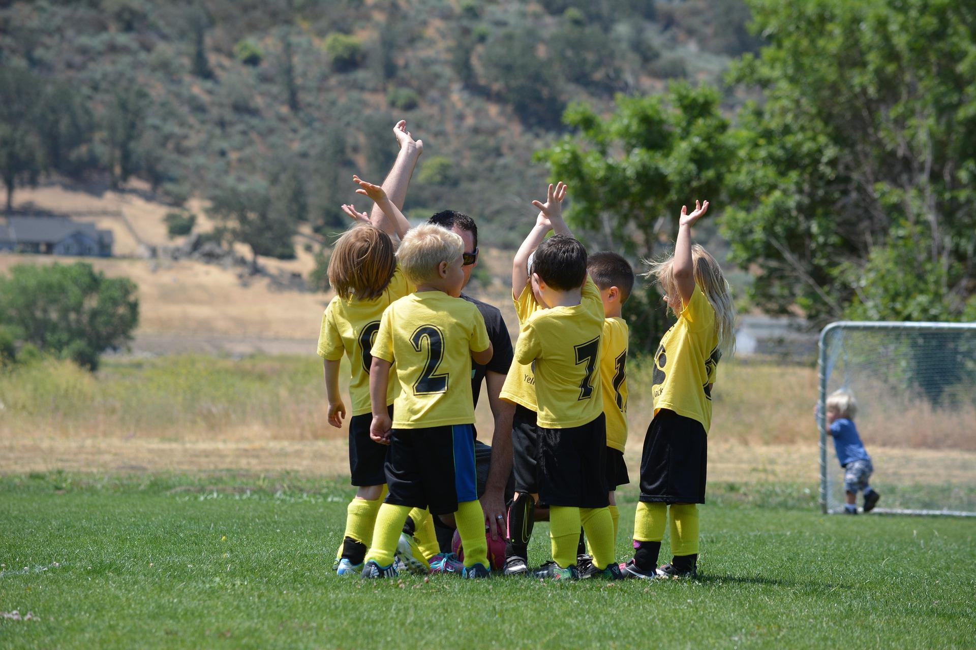 サッカーグランドに立つ5人の外国人の子どもたちと1人のコーチ