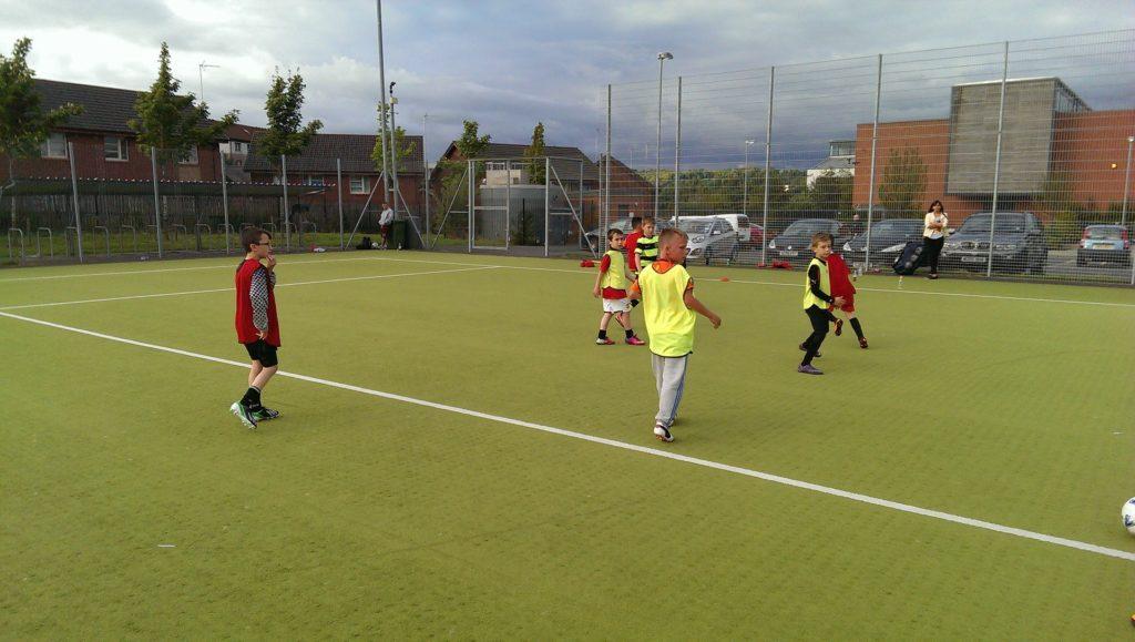 芝生でサッカーをやる子供たち