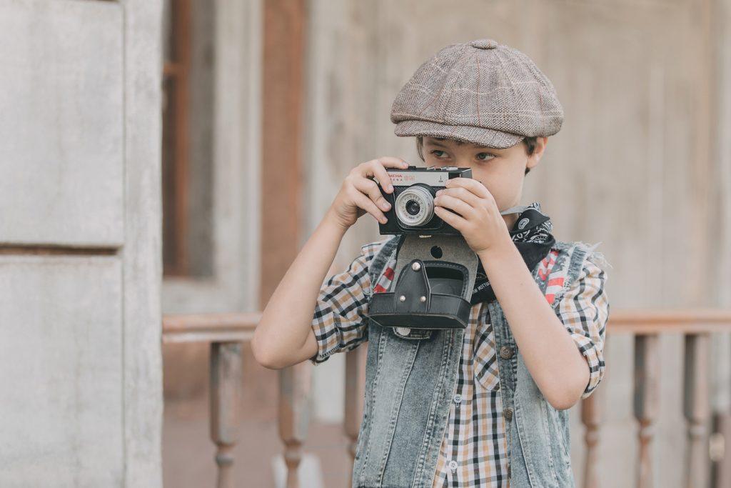 カメラを撮る帽子を被った少年