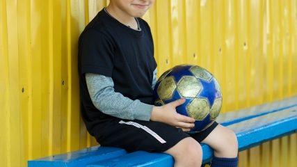 サッカーベンチに座る少年